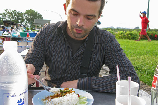 Nik eating Penang Curry with 5-baht water and a bottle of Coca Cola.