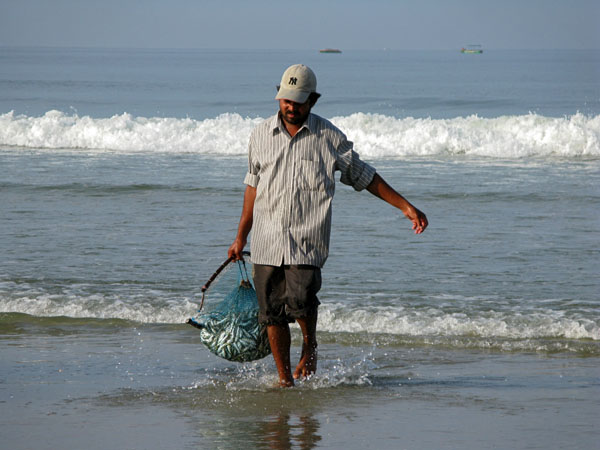 Goa, A local fisherman rinses the mornings catch in the surf