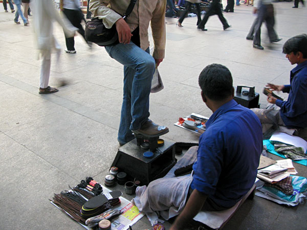 Mumbai, Nik has his shoes shined at the Victoria Terminus Train Station during the morning commute