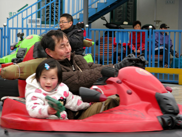 Dad and daughter having fun in the bumper cars at Century Park