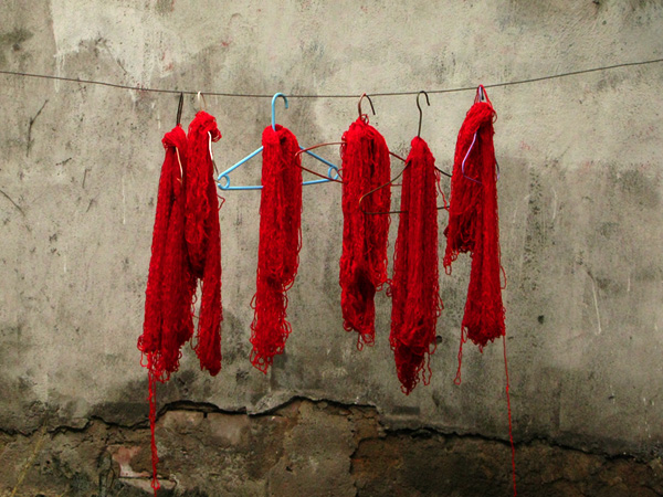 Red hand dyed yarn drying on the side of the street