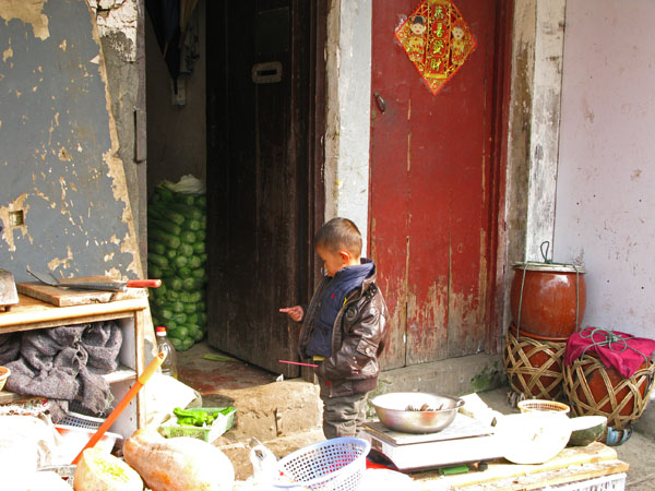 Kid plays with chopstick, Chinese cellery stored in the hallway, fermenting vegetables in pots, huge squash sitting on the sidewalk, knife resting on chopping block